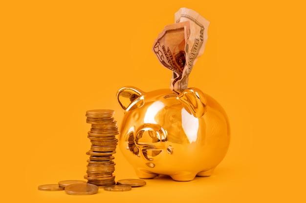 Tirelire dorée avec tour de l'argent et billets en euros sur fond jaune