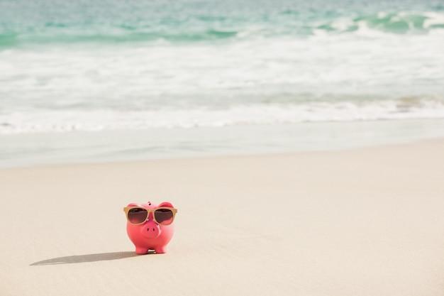 Tirelire d'été avec des lunettes de soleil sur le sable