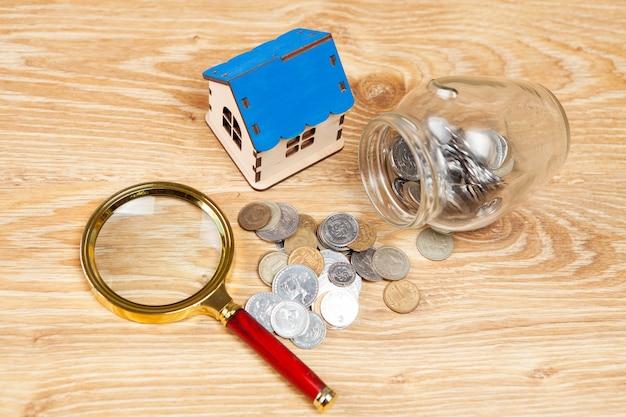Tirelire, loupe et une maison sur une table en bois. concept de recherche à domicile