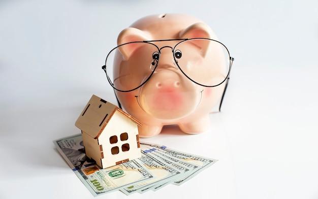 Tirelire avec maison en bois et dollars. isolé sur le mur blanc