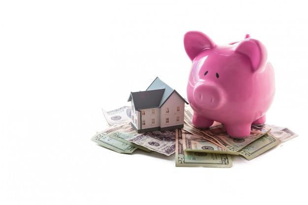 Tirelire et maison miniature reposant sur une pile de dollars