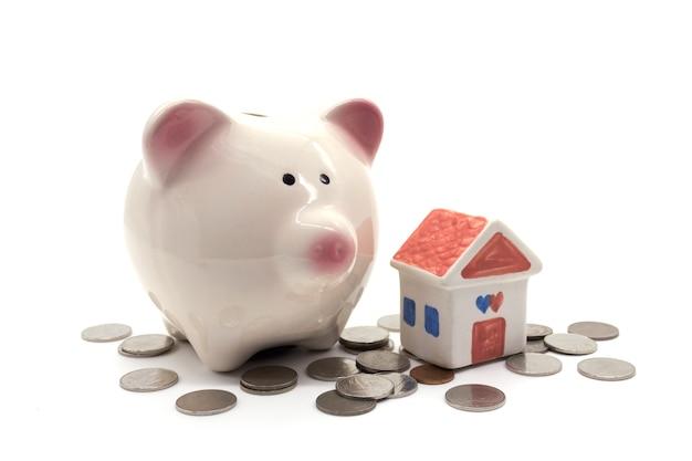 Tirelire avec maison et pièce de monnaie sur fond blanc