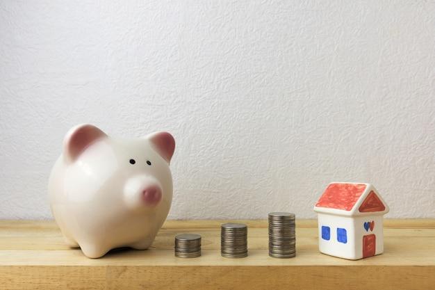 Tirelire avec maison et pièces de monnaie