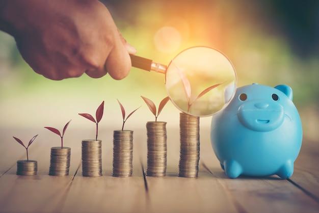 Une tirelire mis sur les pièces d'or empilables et la maison de tableau et l'horloge sur le fond bleu vintage, économiser de l'argent pour acheter un nouveau bien immobilier ou un prêt pour l'investissement planifié dans le futur concept.