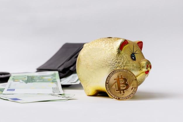 Tirelire d'or avec bitcoin et billets en euros sur fond blanc