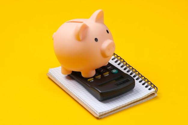 Tirelire, ordinateur portable et calculatrice sur jaune