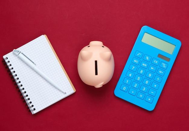 Tirelire, ordinateur portable et calculatrice sur rouge