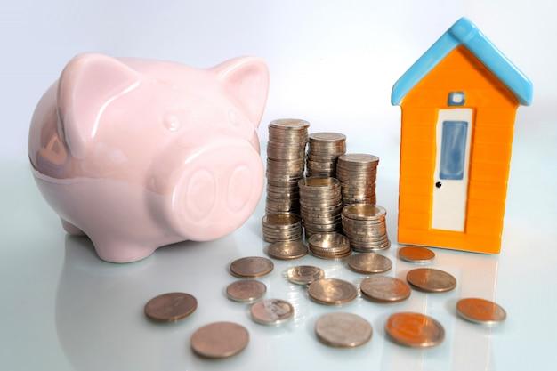 Tirelire avec petite maison et pièce de monnaie sur fond blanc