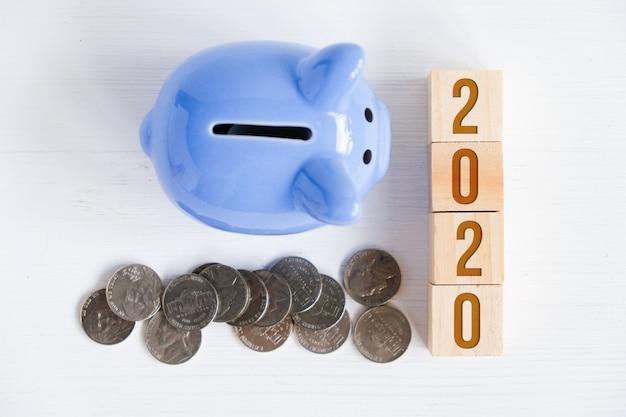 Tirelire, pièces de monnaie dispersées, chiffres symbolisant le nouvel an