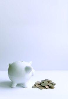 Tirelire avec des pièces de monnaie. tirelire en céramique blanche.