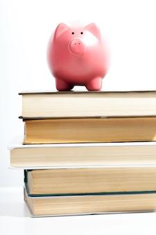 Tirelire sur une pile de livre concept des coûts de l'éducation