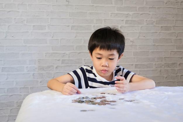 Tirelire pour bébé mettant une pièce de monnaie dans une tirelire - enfant, économiser de l'argent pour le futur concept