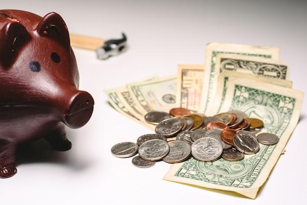 Tirelire pour calculer le budget de début d'année avec des billets d'un dollar et des pièces pour éviter la crise financière.