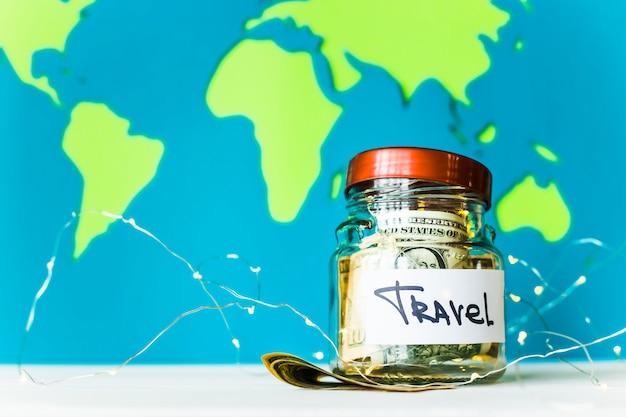 Tirelire pour voyager avec des dollars et guirlandes sur un fond de carte du monde lumineux. argent pour voyager. concept d'accumulation
