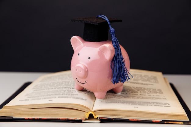 Tirelire rose en casquette. collège, diplômé, concept d'éducation.