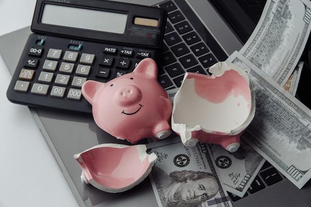 Tirelire rose cassée sur un clavier, une calculatrice et des billets d'un dollar