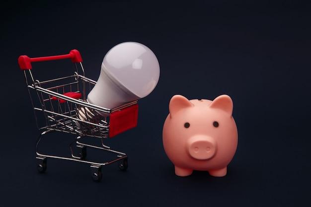 Tirelire rose, chariot et ampoule, concept d'économie d'énergie.