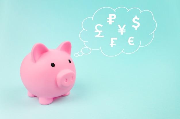 Tirelire rose avec des devises mondiales d'hologramme numérique dans le nuage pensé au-dessus de sa tête sur fond bleu. économiser de l'argent pour le futur concept d'investissement et de retraite.