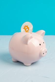 Tirelire rose sur espace bleu avec pièce de bitcoin