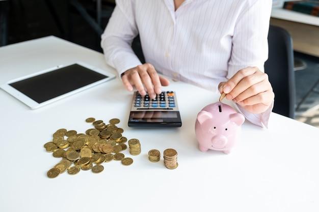 Tirelire rose avec femme d'affaires au bureau, épargner pour un nouvel objectif commercial et un concept de retraite