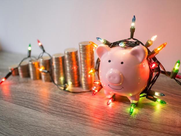 Tirelire rose avec graphique de croissance des piles de pièces et lumières de fête, amusante économie d'argent pour le futur plan d'investissement et le concept de fonds de retraite.