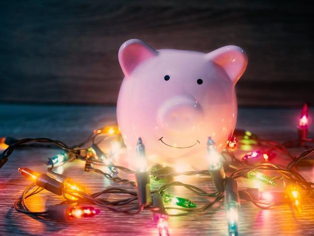 Tirelire rose avec des lumières de fête, profitez d'économies pour le concept de vacances.