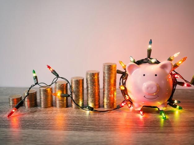 Tirelire rose avec pile de pièces et lumières de fête économisant de l'argent pour le concept de fonds de retraite