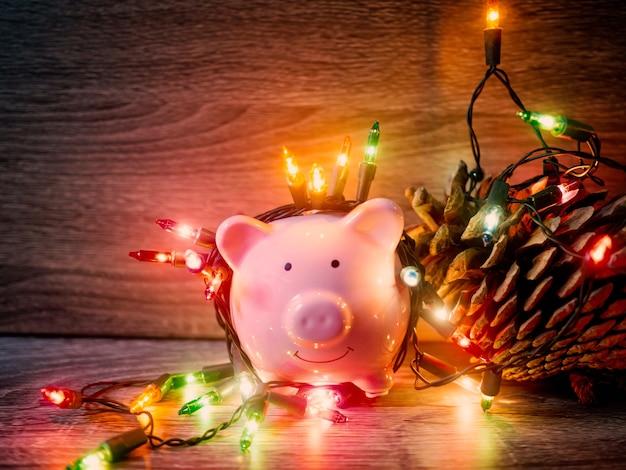 Tirelire rose et pomme de pin avec des lumières de fête, profitez d'économies pour le concept de vacances.