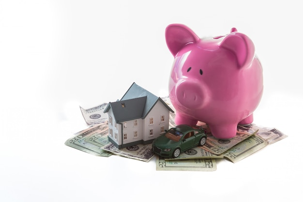 Tirelire voiture miniature et maison miniature reposant sur des tas de dollars sur fond blanc
