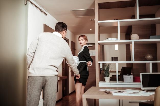 Tirer l'uniforme. client de l'hôtel tirant l'uniforme de la femme de chambre dans sa direction ayant un désir sexuel