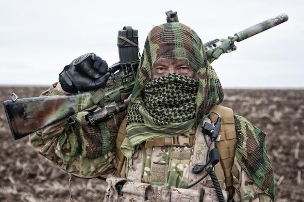 Tireur d'élite de l'armée, joueur d'airsoft en uniforme de camouflage et porte-charge, cape de masquage sur la tête, fusil de service armé avec viseur optique, se cachant le visage avec shemagh, debout sur le terrain, regardant au loin