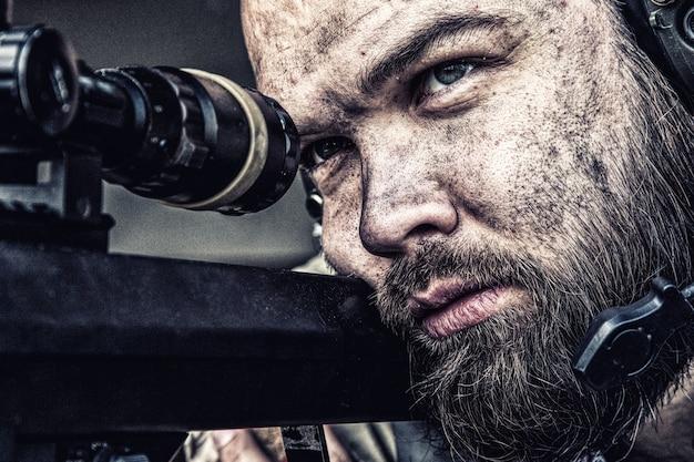 Tireur d'élite de l'armée avec un visage barbu et sale visant avec une lunette optique sur un fusil de sniper, observant le champ de bataille depuis une embuscade et recherchant des cibles à tirer, tirant sur de longues distances, en gros plan