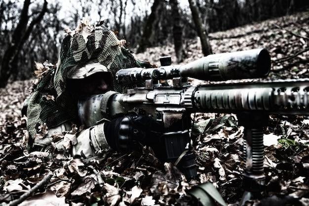Tireur d'élite des forces d'élite de l'armée, tireur d'élite du groupe tactique, joueur d'airsoft allongé sur le sol dans la forêt, se cachant dans le feuillage d'automne, se couvrant d'une cape de camouflage, recherchant des cibles à l'aide d'un viseur optique