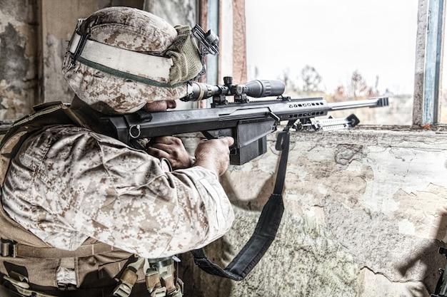 Un tireur d'élite des marines armé d'un fusil de sniper anti-matériel de gros calibre se cachant dans un bâtiment urbain en ruine, tirant sur des cibles ennemies à distance d'un abri, assis dans une embuscade. fusillade militaire en ville