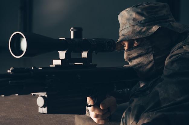 Le tireur d'élite ment et vise à travers la lunette de visée.