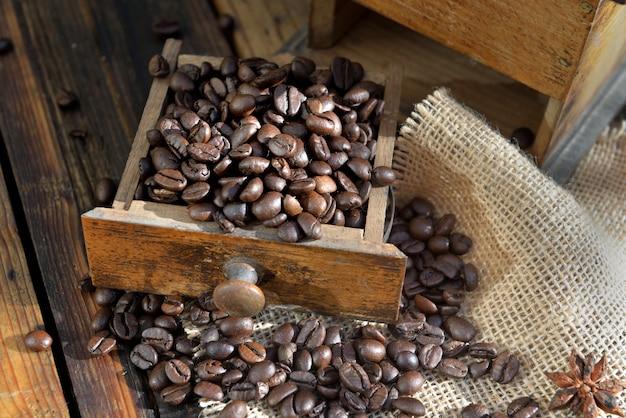 Tiroir d'un moulin à café rempli de grain sur fond de bois rustique