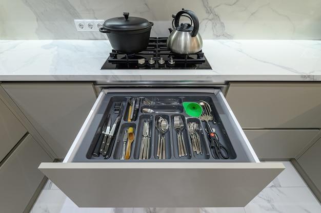 Tiroir ouvert avec couverts dans une cuisine moderne en bois blanc de style classique