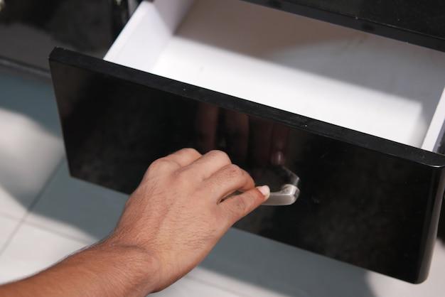 Tiroir ouvert à la main de l'homme en bois dans une armoire