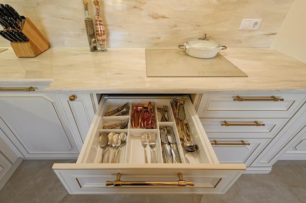Tiroir tiré dans l'armoire au mobilier de cuisine classique beige et or de luxe