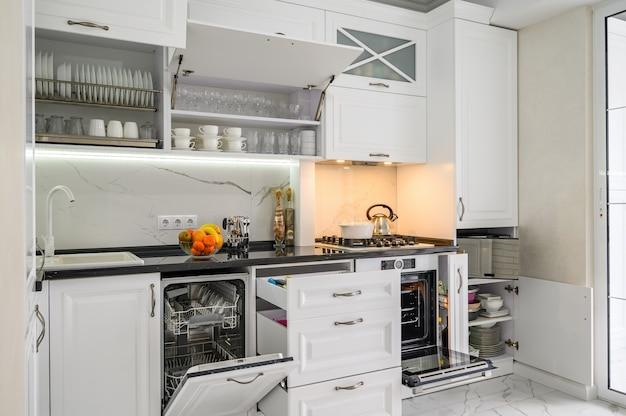Les tiroirs intérieurs de cuisine moderne blanc luxueux ont sorti la porte des fours ouverte