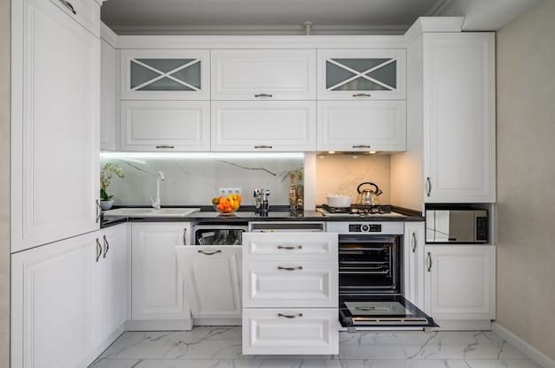 Tiroirs intérieurs de cuisine moderne blanc luxueux sorti lave-vaisselle porte ouverte