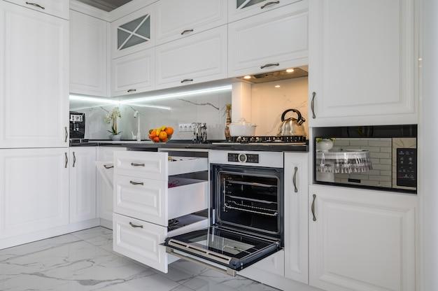 Tiroirs intérieurs de cuisine moderne blanc luxueux sorti la porte du four ouverte