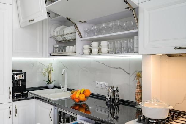 Tiroirs intérieurs de cuisine moderne blanc luxueux tirés portes ouvertes