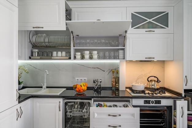Les tiroirs intérieurs de la cuisine moderne blanche luxueuse ont sorti la porte du lave-vaisselle ouverte