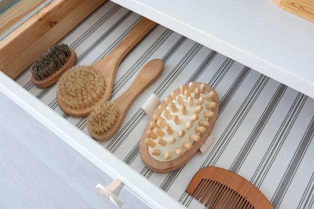 Tiroirs ouverts de coiffeuse avec brosses, masseur et peigne en bois et poils naturels.