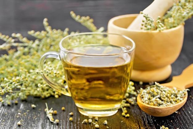 Tisane d'absinthe grise dans une tasse en verre, fleurs d'armoise sèches en cuillère, fleurs fraîches dans un mortier et sur table contre planche de bois noir