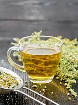 Tisane d'absinthe grise dans une tasse en verre, des fleurs fraîches et une passoire en métal avec des fleurs d'armoise sèches sur fond de planche de bois
