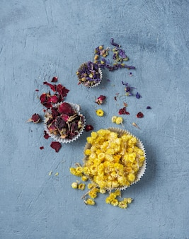 Tisane aromatique camomille, rose et lavande en vrac sur table en bois bleu