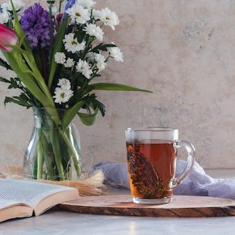Tisane au thym sur blanc avec bouquet de fleurs et livre