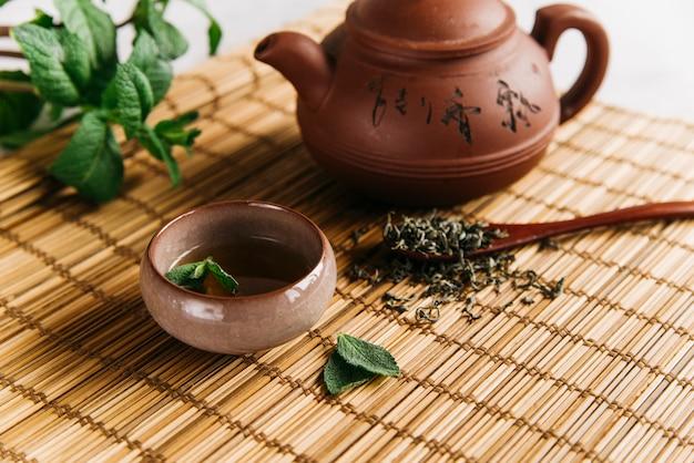 Tisane aux feuilles de menthe et herbes séchées sur napperon